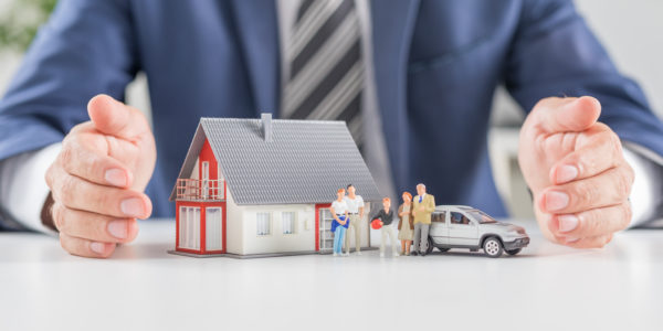 Insurance house, car and family health live concept. The insurance agent presents the toys that symbolize the coverage.